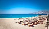 Sunshade umbrellas and deckchairs on the beautiful  Mango beach in Saranda, Albania.