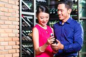 Portrait of Asian couple holding a bottle of wine