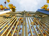 stock photo of gates heaven  - A concept image of the golden gates to heaven shut on an autumn leave and blue sky background - JPG