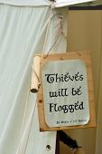 stock photo of flogging  - Thieves will be flogged sign on side of tent - JPG
