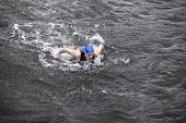 iron man - dynamic and fit swimmer in cap and wetsuit breathing performing the butterfly stroke in dark ocean water