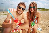 Relaxed young lovers partying on the beach on a sunny day