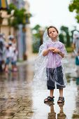 Little boy in plastic transparent raincoat standing under the rain on summer day