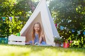 stock photo of tipi  - Adorable little girl having fun playing in a canvas tent outdoors on summer day - JPG