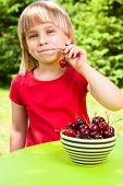 Cute little girl eating sweet cherry outdoors
