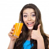 Young cheerful woman drinks orange juice and showing thumb up over white.