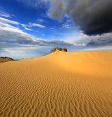 Scene with dunes in sandy desert before thunder storm