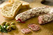 A Salami with baguette and green olives