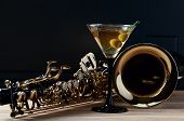 stock photo of saxophones  - saxophone and martini with green olives on wooden table - JPG