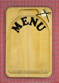 Menu sign with heart on wood cutting board with red checkered (gingham) tablecloth