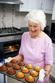 Happy old lady taking muffins out of the oven