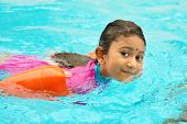 Asian girl in swimmer class with float bands. Indian child learning swimming in pool.