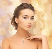 beauty and jewelry concept - woman wearing shiny diamond pendant