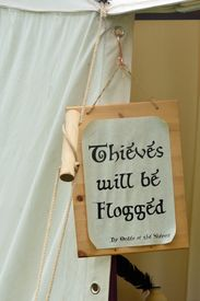 image of flogging  - Thieves will be flogged sign on side of tent - JPG