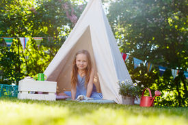 picture of tipi  - Adorable little girl having fun playing in a canvas tent outdoors on summer day - JPG