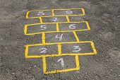 stock photo of hopscotch  - Figures in childish game hopscotch painted with yellow paint on asphalt - JPG