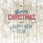 Merry Christmas greeting on blond wooden background