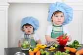 Little girl in kitchen apron and cap with large red pepper and small boy