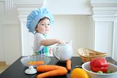 Small girl in kitchen apron and cap standing at table with white teapot and vegetables