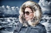 Grunge style photo of luxury woman portrait in wintertime outdoors, wearing stylish sunglasses and warm coat with furry hood and looking away, fashionable winter style concept