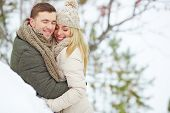 Young man embracing his girlfriend in winter day
