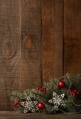 Fir branch with Christmas decoration on  old wooden plank.
