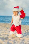 Little Santa boy on the beach. Tropical Christmas