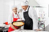 Portrait of happy female chef standing by colleague holding pizza pan at commercial kitchen