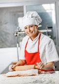 Portrait of smiling female chef rolling pasta sheet at counter in commercial kitchen