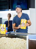 Portrait of happy male worker holding popcorn paperbag while colleague in background at cinema concession stand