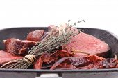 fresh ripe marble beef meat on barbecue pan with thyme and pepper isolated on white background