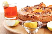 sweet round apple pie on wooden plate served with fresh lemon, mandarin, and cinnamon sticks on table