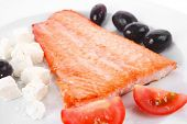red salmon fish big fillet chunk roast and served on plate with greek white cheese black olives and tomatoes isolated over white background