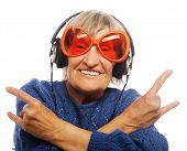 Funny old lady listening music and showing thumbs up. Isolated on white.
