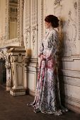 Young beautiful woman standing in the palace room.