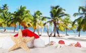 Champagne flutes with santa cap on sunny beach, celebration theme.