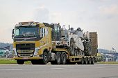 Yellow Volvo FH Hauls Heavy Machinery