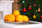 Sweet tangerines on plate in room on Christmas tree background