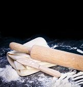 Classic wooden rolling pin with freshly prepared dough and dusting of flour on black background