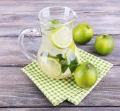 Lemonade in pitcher on wooden background