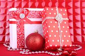 Beautiful bright gifts and Christmas decoration on red background