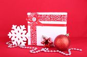 Beautiful bright gift and Christmas decoration on red background