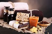 Organic soap with coffee beans, sea salt on wicker mat, on  table, on dark background Coffee spa concept
