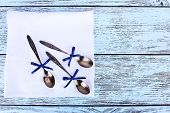 Metal spoons on white napkin on wooden background