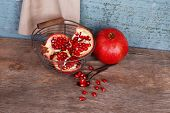 Juicy ripe pomegranates on old wooden table