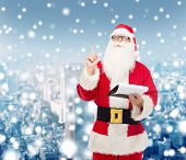 christmas, holidays, gesture and people concept - man in costume of santa claus with notepad pointing finger up over snowy city background
