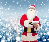 christmas, holidays and people concept - man in costume of santa claus with notepad and pen over snowy city background