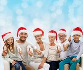 family, generation, gesture, holidays and people concept - happy family in santa helper hats showing thumbs up over blue lights background