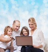 family, holidays, shopping, technology and people - happy family with laptop computer and credit card over blue lights background