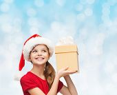 christmas, holidays, childhood and people concept - smiling girl in santa helper hat with gift box over blue lights background